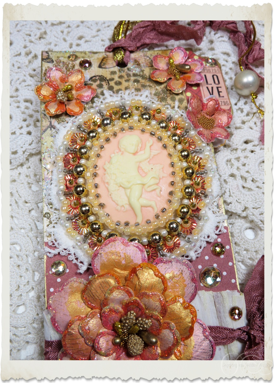 Details of handmade angel cameo with bead embroidery on lace surrounded with paper flowers and glittery details