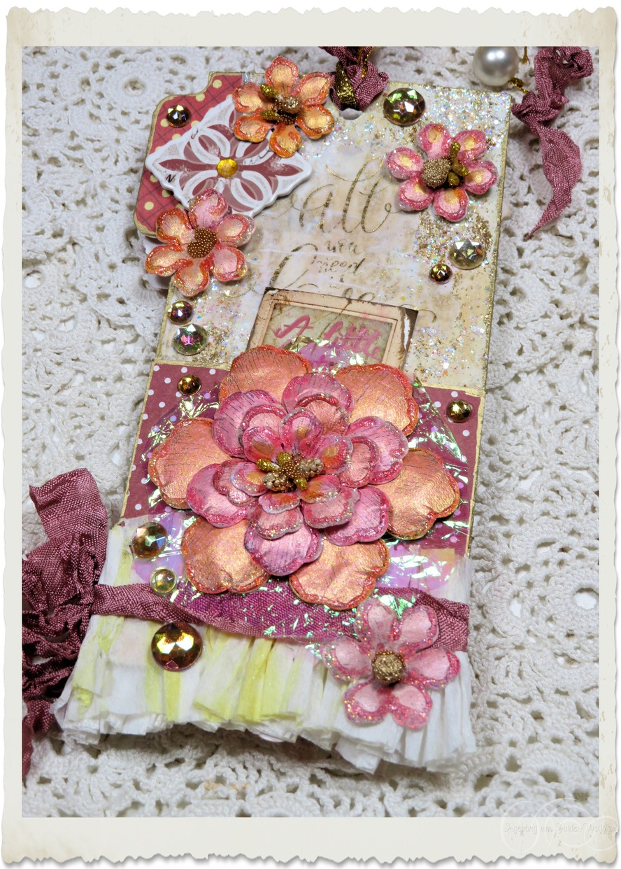 Backside of handmade paper tag with peach pink paper flowers and golden bling details